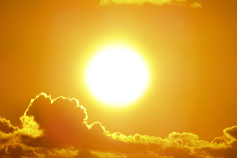 Bright sun glowing with golden clouds