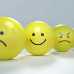 Yellow balls lined up with faces drawn on displaying different emotions