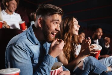 Image of laughing friends sitting in cinema