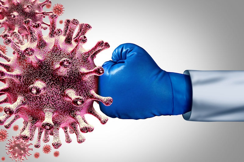 Covid-19 virus being hit by a doctor wearing a boxing glove