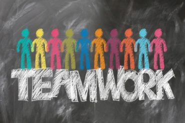 Blackboard with multi-colored people and the word teamwork drawn on