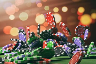 colored casino chips falling onto a roulette table