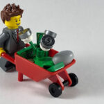 Lego character wheeling a barrow of money plants