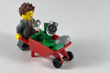 Lego character wheeling a barrow of money plants