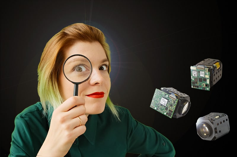Woman looking through magnifying glass taking closer look at our cameras