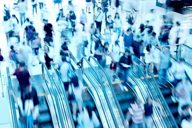 Fast-moving shoppers on an escalator in a shopping mall